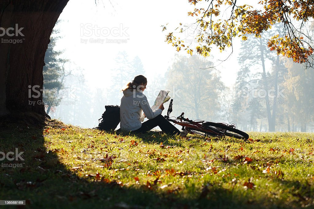 Woman cyclist with read the map sitting among green scenery royalty-free stock photo