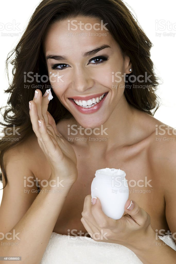 Woman dabbing cold cream on her face royalty-free stock photo