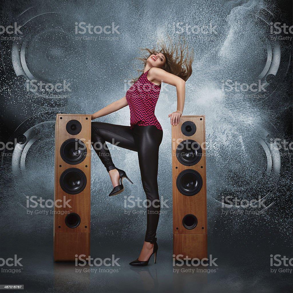 Woman dancing against of powerful speakers stock photo