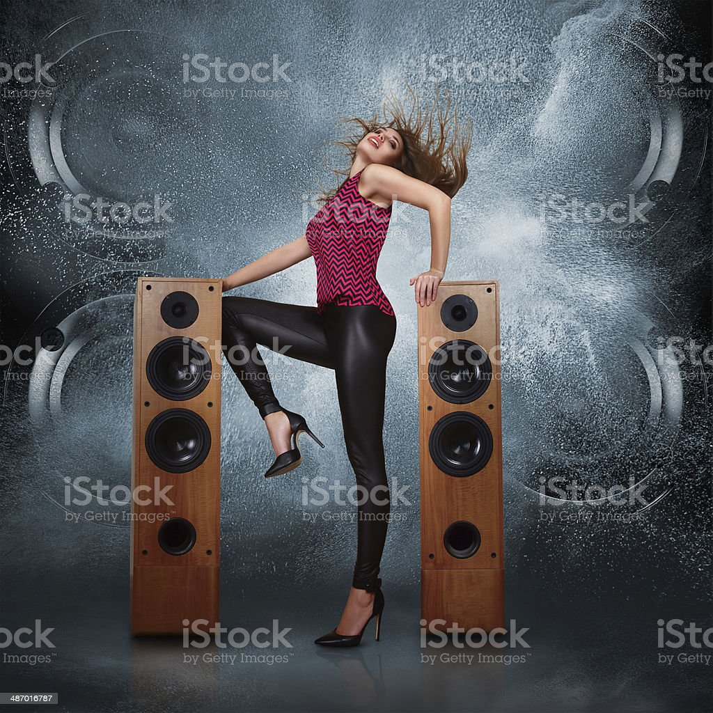 Woman dancing against of powerful speakers stock photo