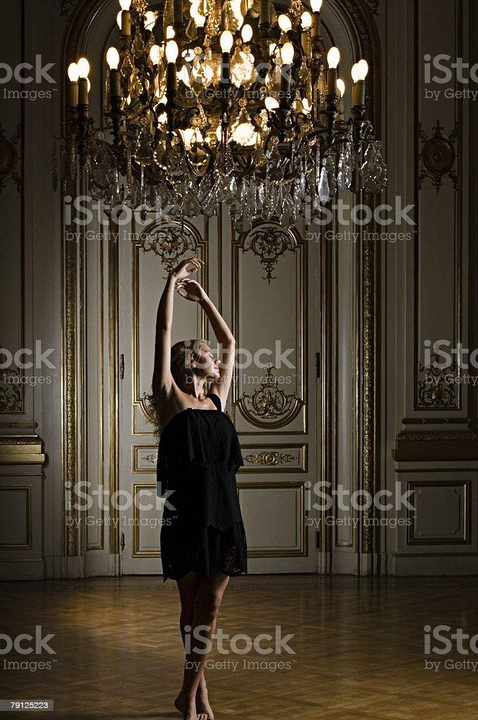 Woman dancing beneath chandelier stock photo