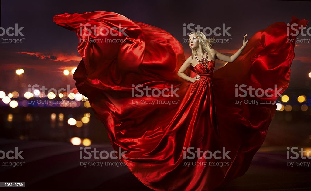 woman dancing in silk dress, artistic red blowing gown fabric stock photo