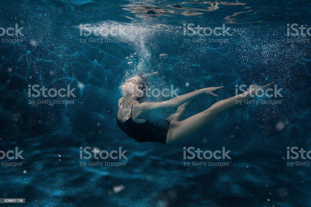 Woman dancing in the underwater. stock photo