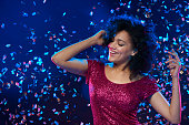 Woman dancing on a party over colorful background with confetti