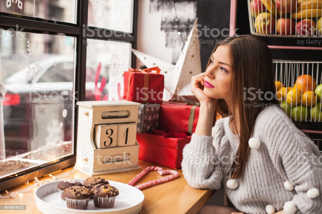 Woman daydreaming in coffee shop stock photo