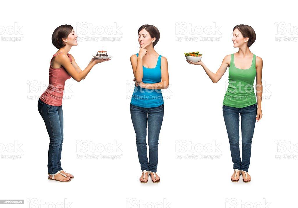 Woman deciding between cake or salad stock photo