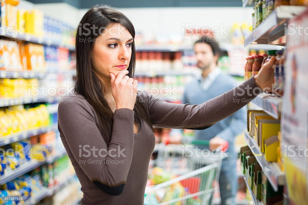 Woman deciding on purchases in a supermarket stock photo