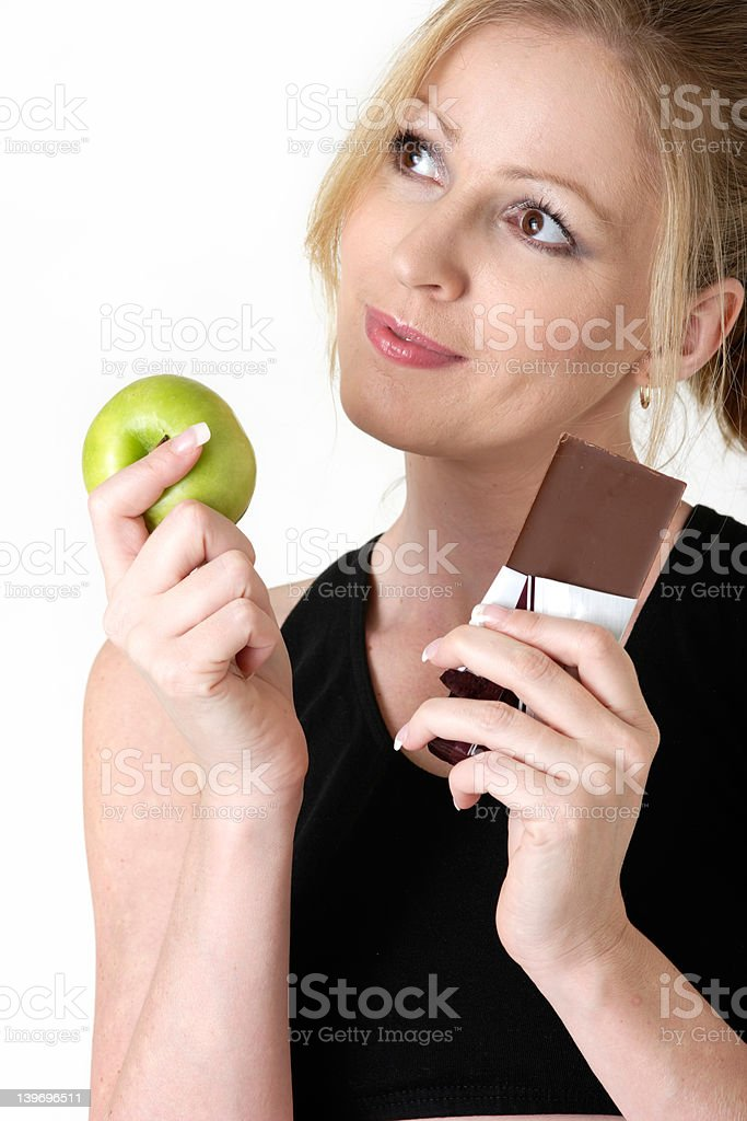 woman deciding whether to eat apple or chocolate royalty-free stock photo