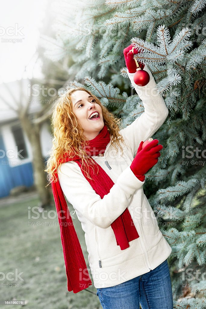 Woman decorating Christmas tree outside royalty-free stock photo