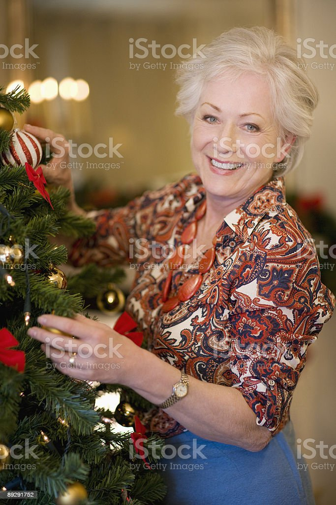 Woman decorating Christmas tree royalty-free stock photo