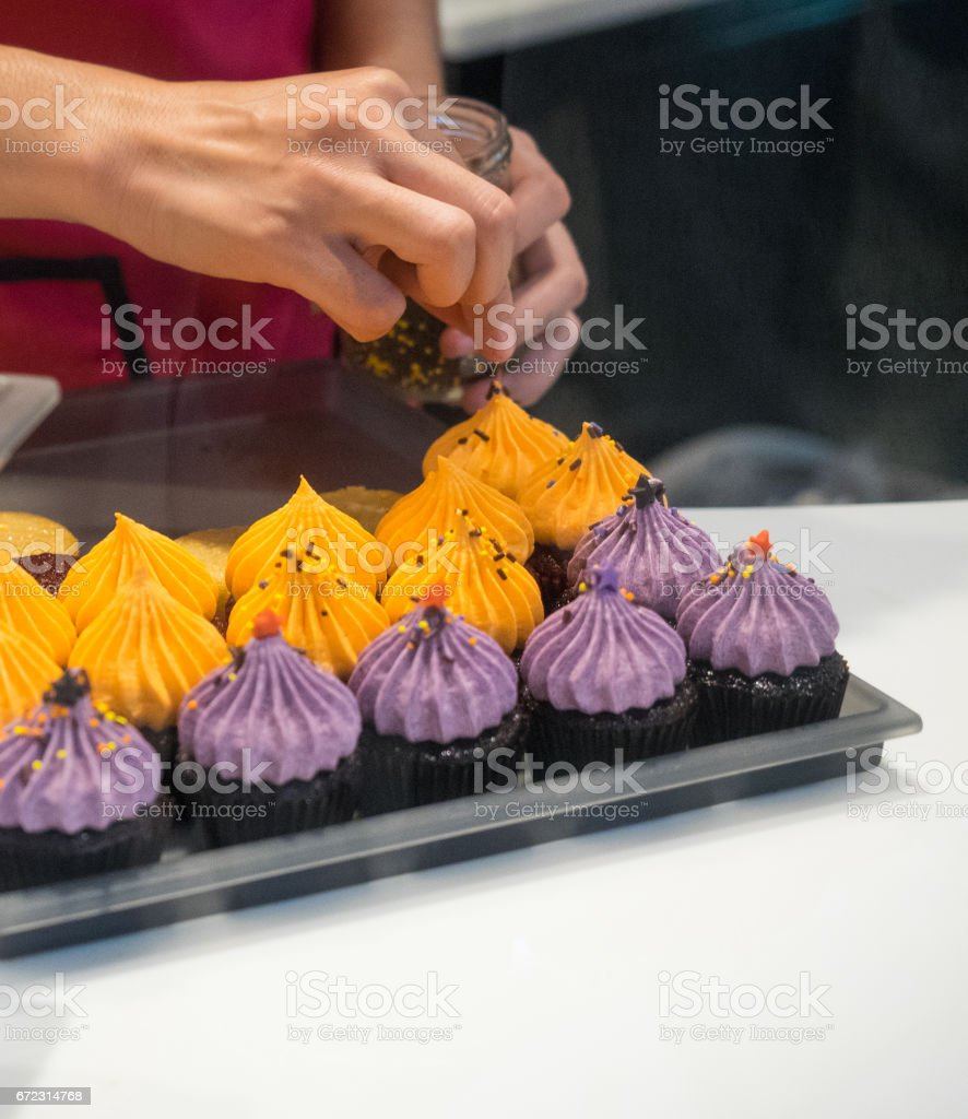 woman decorating halloween cupcakes royalty free stock photo