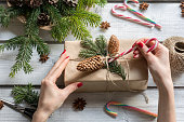 Woman decorating present with candy cane, cones and spruce branch