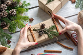 Woman decorating present with cinnamon sticks, cones and spruce branch