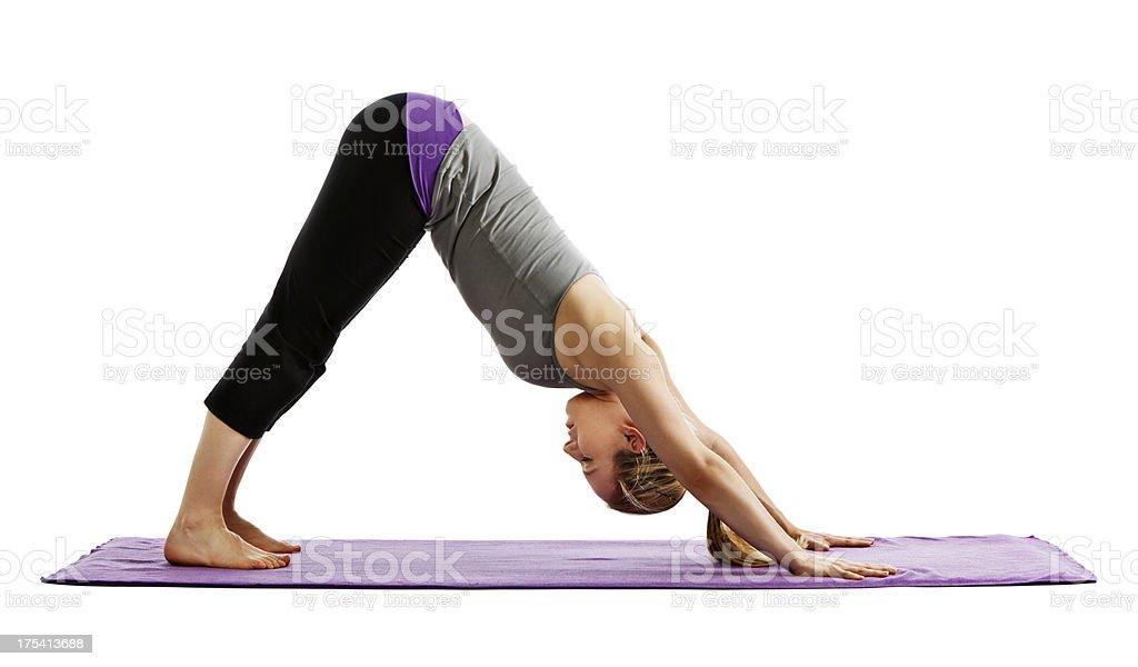 Woman demonstrates downward facing dog yoga pose stock photo
