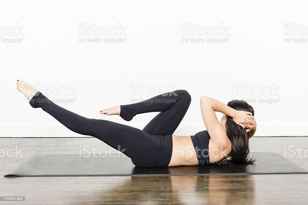 A woman demonstrating a bicycle crunch yoga pose stock photo