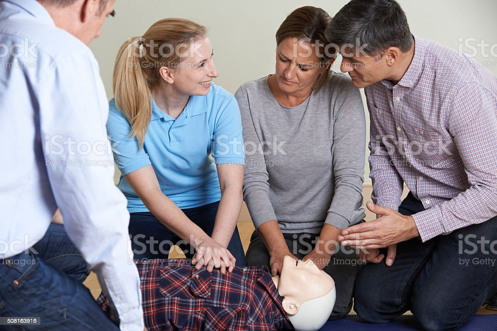 Woman Demonstrating CPR On Training Dummy In First Aid Class stock photo
