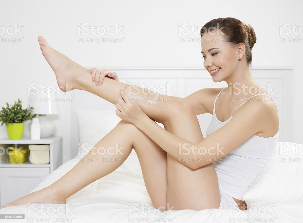 woman depilating skin on legs by waxing royalty-free stock photo