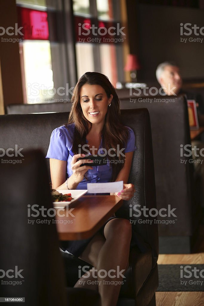 Woman Depositing Check Through Mobile Phone At Restaurant stock photo