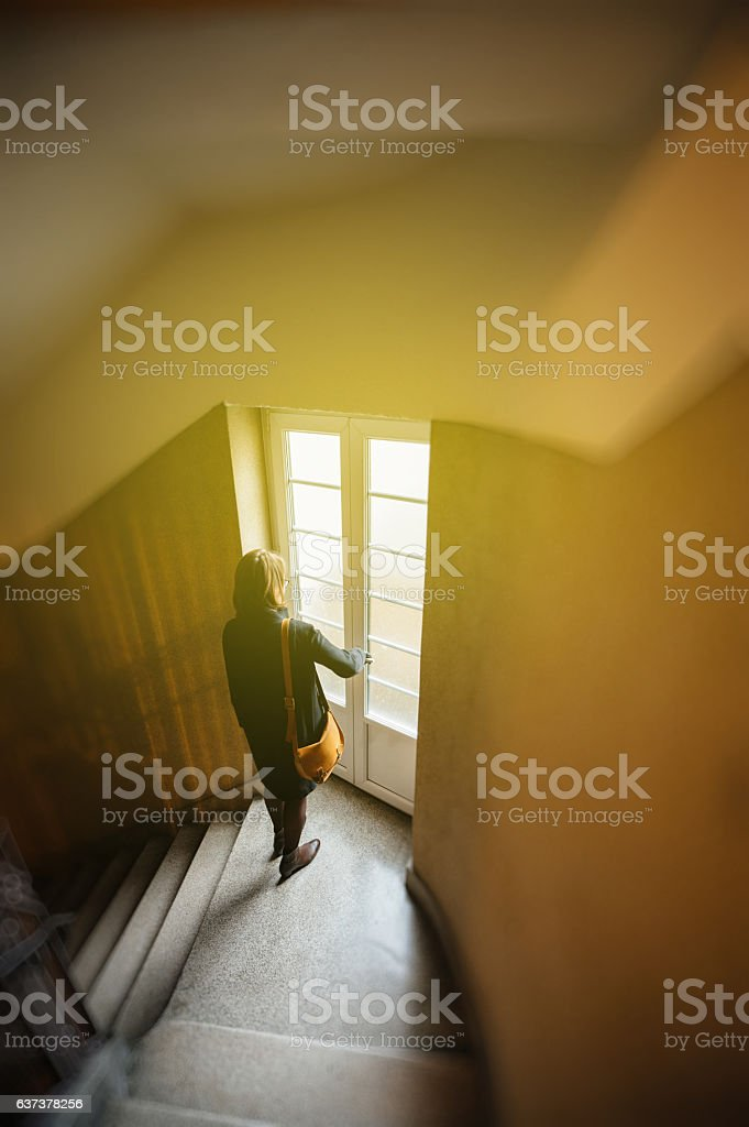 Woman descending stairs in old building stock photo