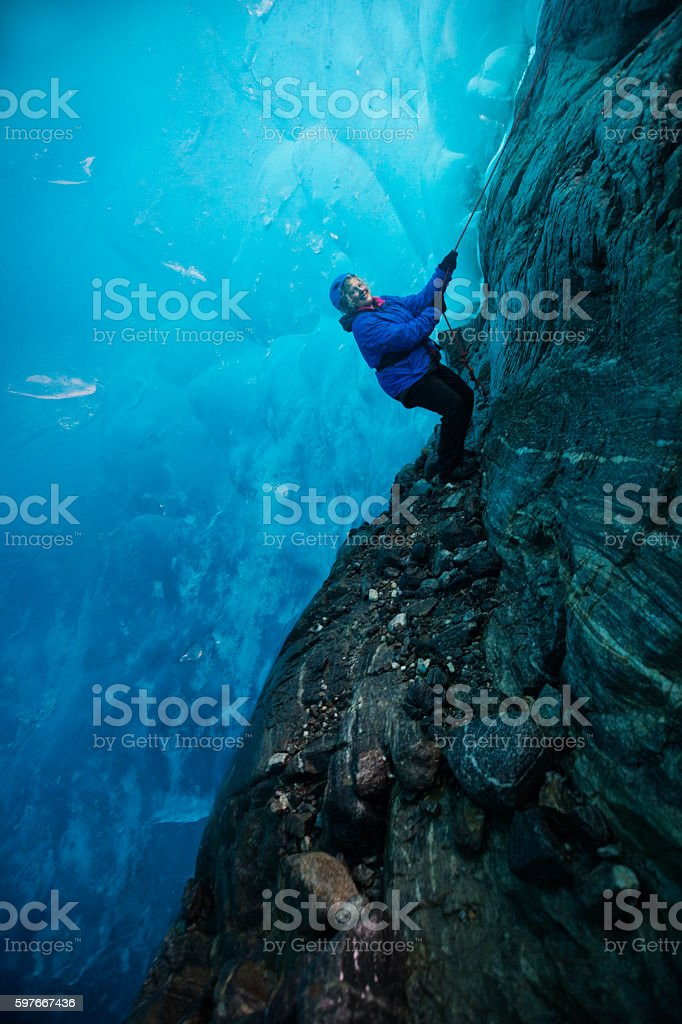 Woman descends into blue ice cave by rope stock photo
