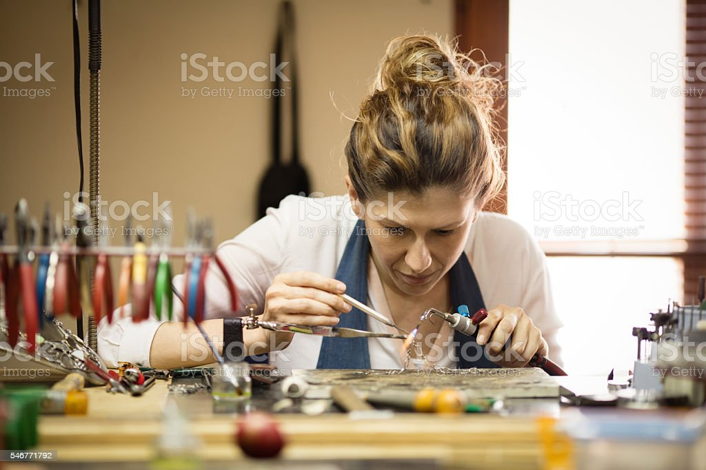 Woman designer makes and design jewelry in workshop stock photo
