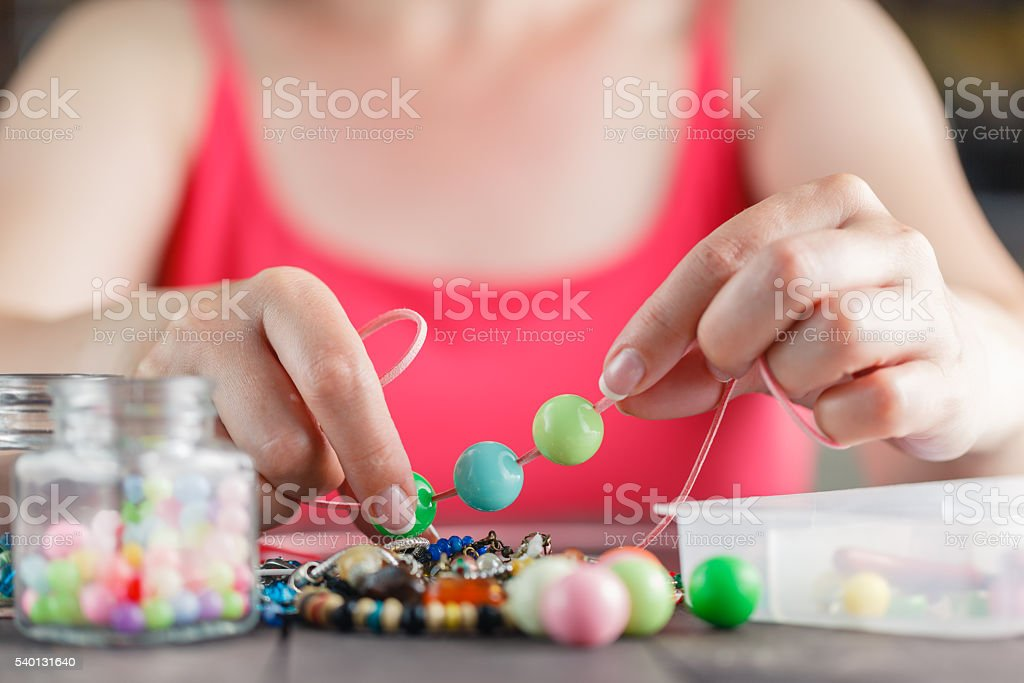 Woman designing colorful necklace with plactic beads stock photo