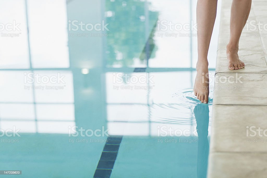 Woman dipping toe in swimming pool stock photo