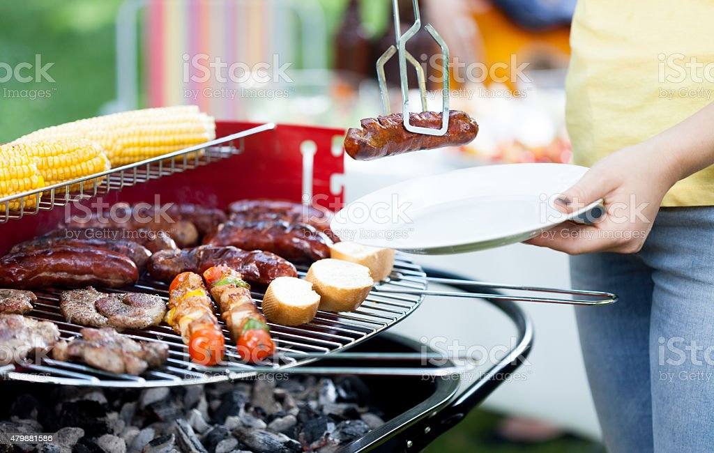 Woman dishing out grilled sausage stock photo