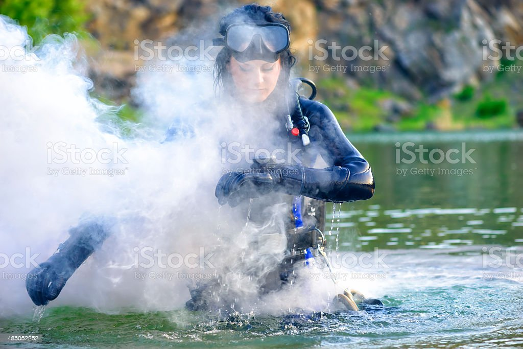 woman diver cheking her gear and smoke stock photo