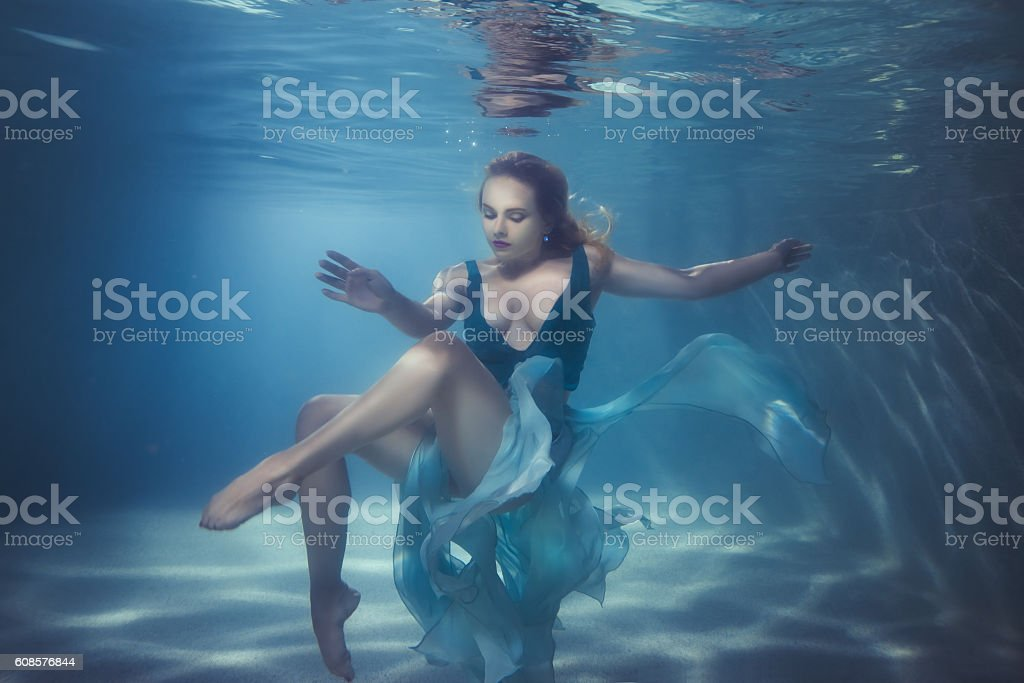 Woman dives underwater. stock photo