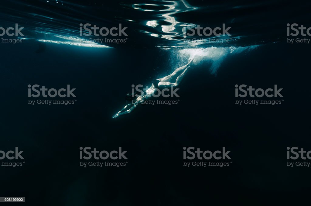 Woman diving into dark water stock photo