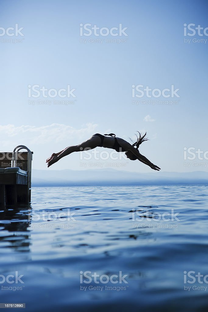 Woman diving into the lake with the sky in the background royalty-free stock photo