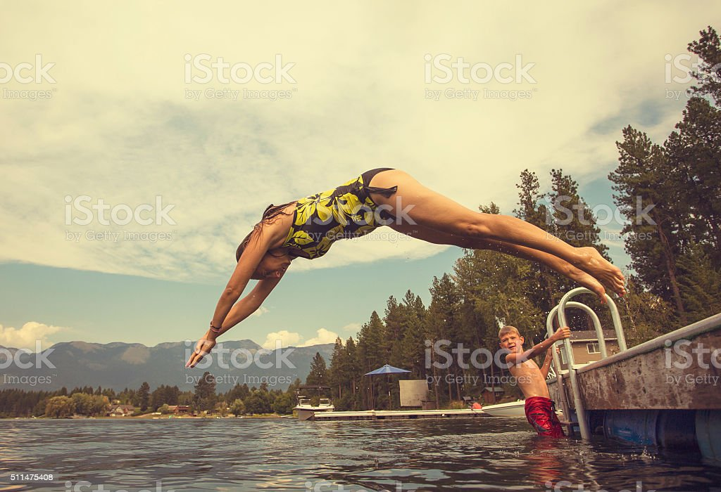 Woman diving off dock of lake while on summer vacation stock photo