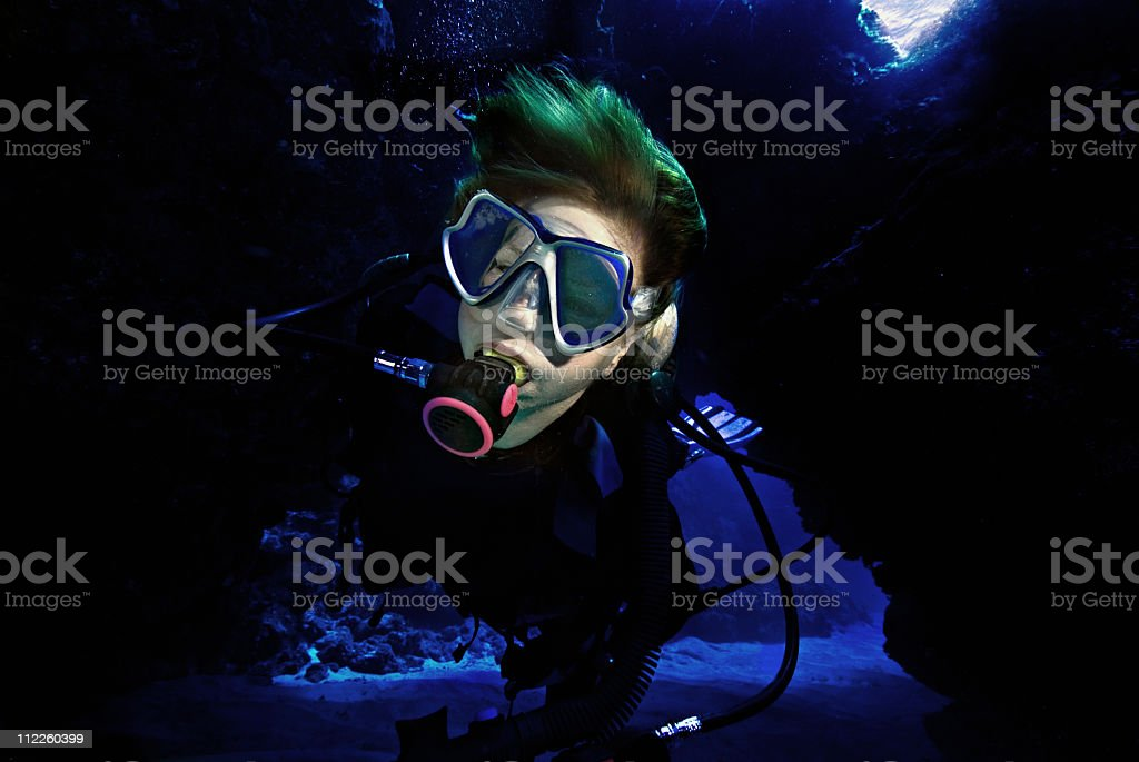 woman diving through a cave stock photo