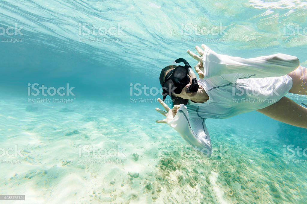 Woman Diving Underwarter Signing OK to the Camera stock photo