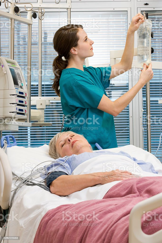 Woman Doctor Checking Patient's IV in ICU stock photo