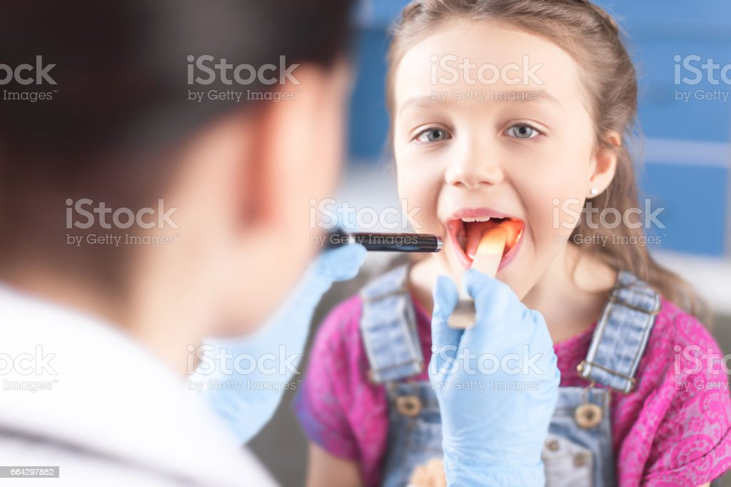 Woman doctor examining throat of little girl with spatula and flashlight stock photo