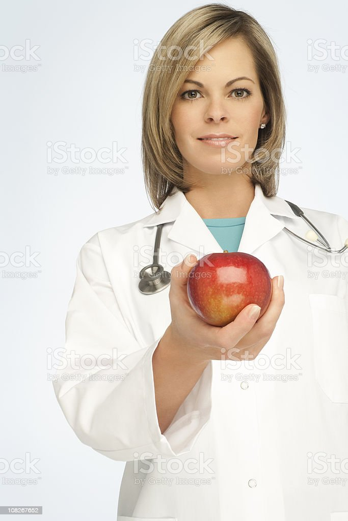 Woman Doctor Recommanding An Apple royalty-free stock photo