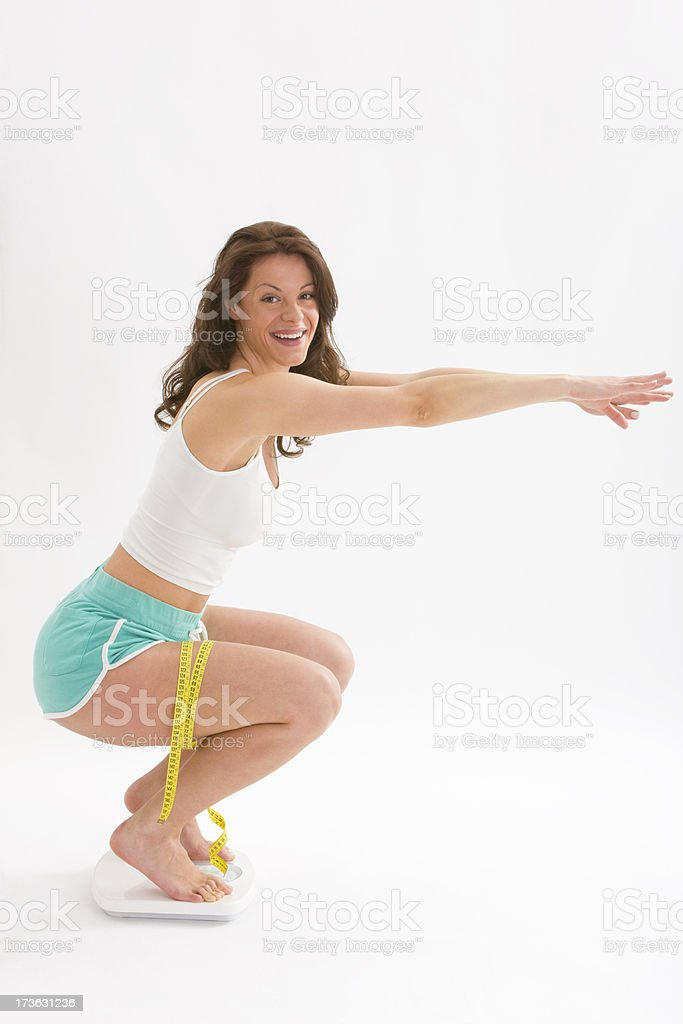 Woman does knee squats on scale royalty-free stock photo