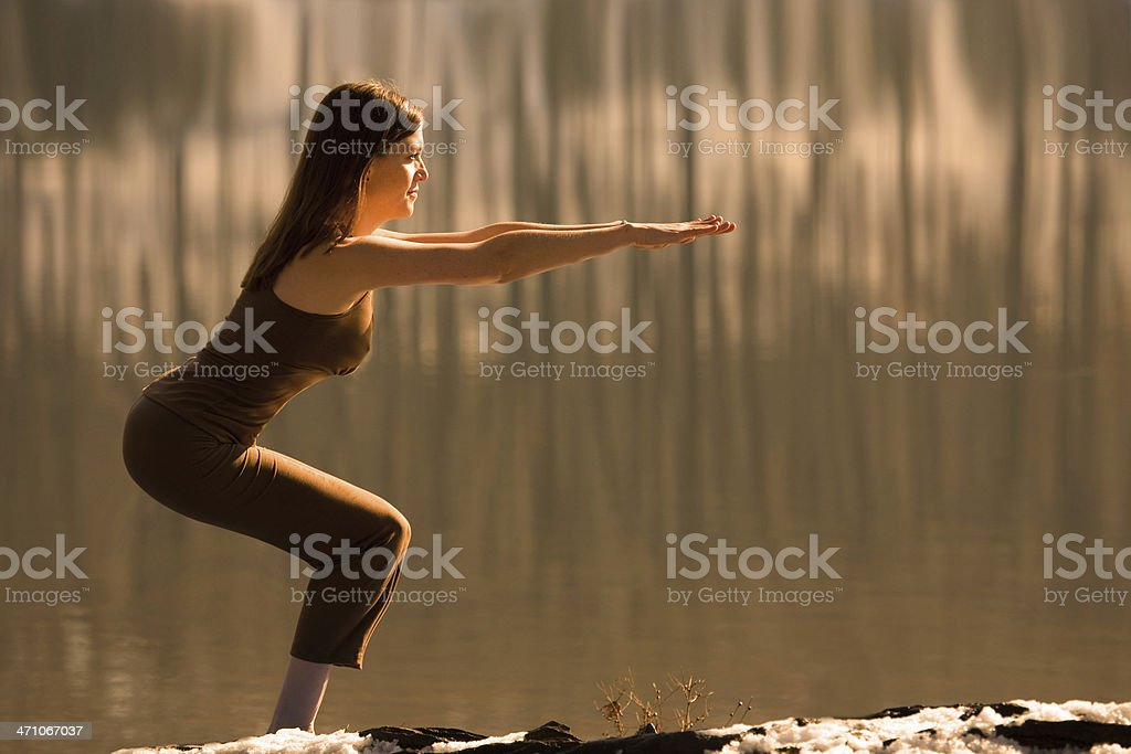 Woman does Yoga 'Chair Pose' next to a Lake stock photo