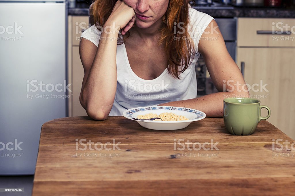 Woman doesn't want to eat her cereal stock photo