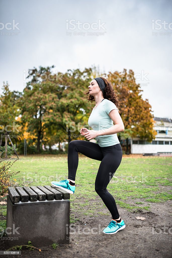 woman doing a   exercise in a park stock photo