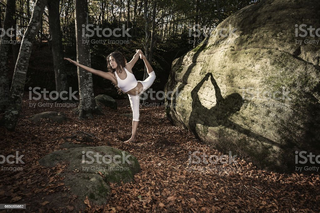 Woman doing a lord of the dance yoga pose stock photo