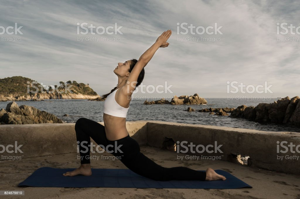Woman doing a low lunge yoga pose at the sea stock photo