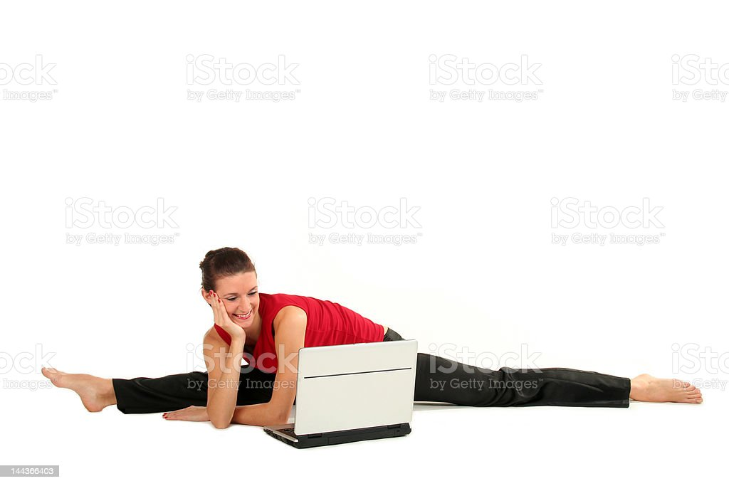 Woman doing a split and using laptop royalty-free stock photo