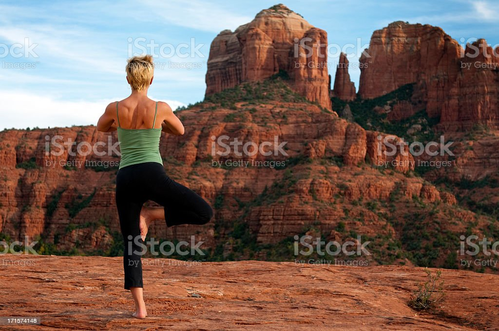 A woman doing a yoga pose in a desert environment stock photo