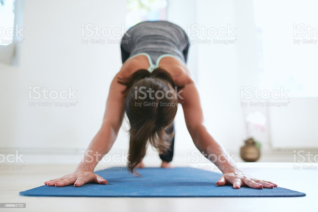 Woman doing Adho Mukha Svanasana yoga pose stock photo
