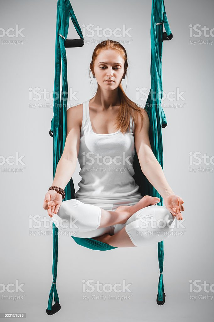 Woman doing antigravity, fly, aerial yoga positions in hammock stock photo