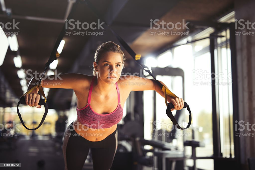 Woman doing arm exercises with suspension straps at gym. stock photo