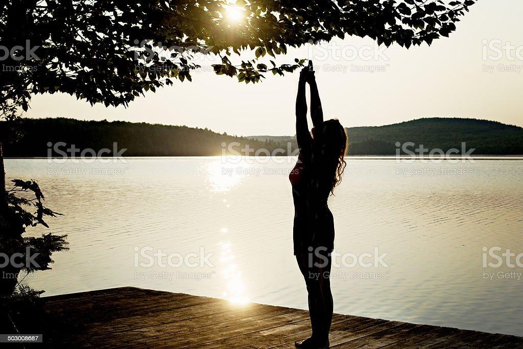 woman doing asana yoga at sunrise at lake stock photo